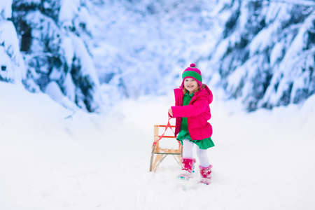 winter fashion: Little girl enjoying a sleigh ride. Child sledding. Toddler kid riding a sledge. Children play outdoors in snow. Kids sled in the Alps mountains in winter. Outdoor fun for family Christmas vacation. Stock Photo