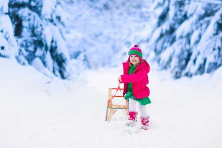 Meisje genieten van een sledetocht. Kind sleeën. Peuter jongen rijden op een slee. De kinderen spelen buiten in de sneeuw. Kinderen slee in de bergen Alpen in de winter. Outdoor plezier voor familie kerstvakantie.
