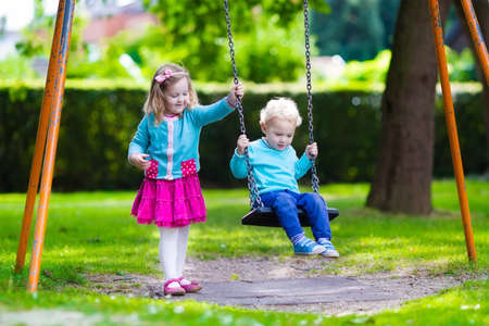 girl on swing: Little boy and girl on a playground. Child playing outdoors in summer. Kids play on school yard. Happy kid in kindergarten or preschool. Children having fun at daycare play ground. Toddler on a swing.