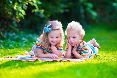 gemelas: Niños que leen un libro en el jardín de verano. Estudio de niños. Juego del muchacho y de la muchacha en el patio de la escuela. Amigos en edad preescolar juegan y aprenden. Hermanos hacer la tarea. Niño de Kindergarten y niños pequeños leen libros.