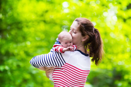 new baby: Mother holding newborn baby in a park. Mom playing with her new born son in the garden. Family with kids play outdoors. Young woman hugging little boy. Parents and children having fun in summer.