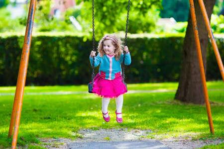 columpios: Niño pequeño y muchacha en un patio de recreo. Niño que juega al aire libre en verano. Los niños juegan en el patio de la escuela. Niño feliz en el kinder o preescolar. Los niños se divierten en el patio de recreo guardería. Niño en un columpio. Foto de archivo