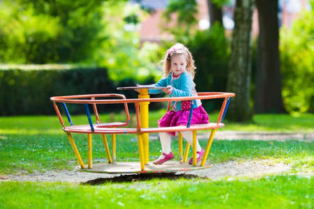 Little girl on a playground. Child playing outdoors in summer. Kids play on school yard. Happy kid in kindergarten or preschool. Children having fun at daycare play ground. Toddler on a slide.