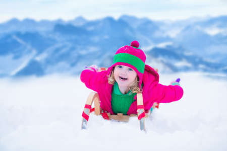 winter vacation: Little girl enjoying a sleigh ride. Child sledding. Toddler kid riding a sledge. Children playing outdoors in snow. Kids sled in the Alps mountains in winter. Outdoor fun for family Christmas vacation