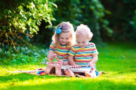 kindergarten education: Kids reading a book in summer garden. Children study. Boy and girl play in school yard. Preschool friends playing and learning. Siblings doing homework. Kindergarten kid and toddler read books.