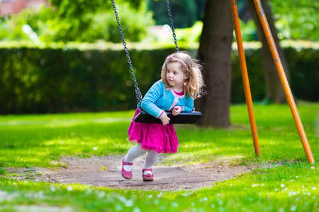 blonde boy: Little girl on a playground. Child playing outdoors in summer. Kids play on school yard. Happy kid in kindergarten or preschool. Children having fun at daycare play ground. Toddler on a swing.