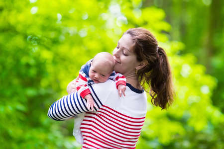 new born baby girl: Mother holding newborn baby in a park. Mom playing with her new born son in the garden. Family with kids play outdoors. Young woman hugging little boy. Parents and children having fun in summer.