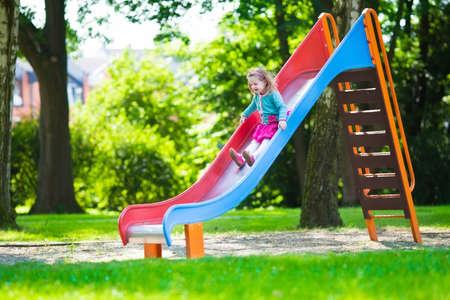 kinder: Niña en un patio de recreo. Niño que juega al aire libre en verano. Los niños juegan en el patio de la escuela. Niño feliz en el kinder o preescolar. Los niños se divierten en el patio de recreo guardería. Niño en una diapositiva. Foto de archivo