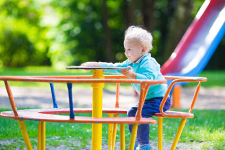 ground: Little boy on a playground. Child playing outdoors in summer. Kids play on school yard. Happy kid in kindergarten or preschool. Children having fun at daycare play ground. Toddler on a swing.