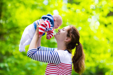 Mother holding newborn baby in a park. Mom playing with her new born son in the garden. Family with kids play outdoors. Young woman hugging little boy. Parents and children having fun in summer.