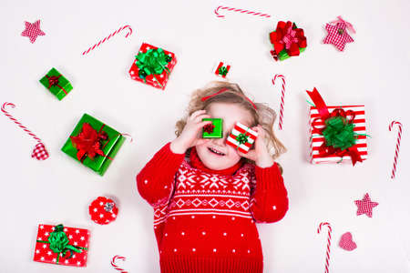 ni�as peque�as: Abrir los regalos de Navidad para ni�os. Ni�a en invierno su�ter de punto con el cuadro actual. Los ni�os abren los regalos. Ni�o del ni�o en el suelo bajo el �rbol de Navidad decorado. Juego de ni�os con caja de regalo y dulces.