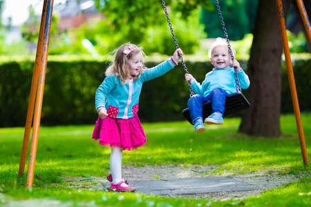 columpio: Niño pequeño y muchacha en un patio de recreo. Niño que juega al aire libre en verano. Los niños juegan en el patio de la escuela. Niño feliz en el kinder o preescolar. Los niños se divierten en el patio de recreo guardería. Niño en un columpio. Foto de archivo
