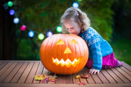 treat: Little girl carving pumpkin at Halloween. Dressed up child trick or treating. Kids trick or treat. Child in witch costume playing in autumn park. Toddler kid with jack-o-lantern.
