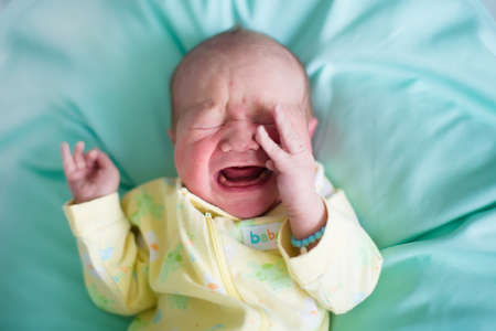 Newborn baby boy in bed. New born child sleeping on a green blanket. Children sleep. Bedding for kids. Infant napping in bed. Healthy little kid shortly after birth. Tired baby yawning.