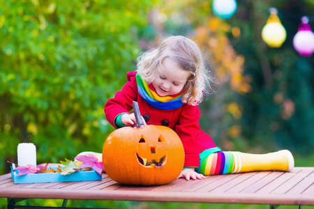Little girl carving pumpkin at Halloween Stock Photo