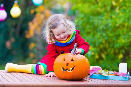 trick: Little girl carving pumpkin at Halloween Stock Photo