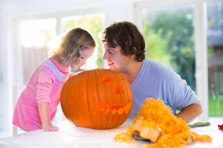 Family carving pumpkin at Halloween. Parents and children decorate the house. Kids and parents trick or treat. Father and child carve squash at home. Toddler kid with jack-o-lantern. Stock Photo
