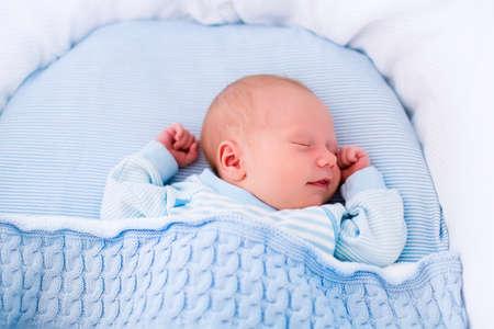 nacimiento bebe: Beb� reci�n nacido en la cama. Ni�o reci�n nacido durmiendo bajo una manta de punto azul. Duermen los ni�os. Ropa de cama para los ni�os. Siesta infantil en la cama. Ni�o sano poco despu�s del nacimiento. Cable tejer textil. Foto de archivo