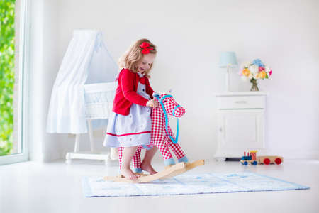 juguete: Los niños juegan en el interior. Niños montar juguete caballito de madera. Niña que juega en la guardería o jardín de infancia. Hermosa guardería para el bebé y niño pequeño. Juguetes para niños de preescolar. Niño lindo divertirse en casa