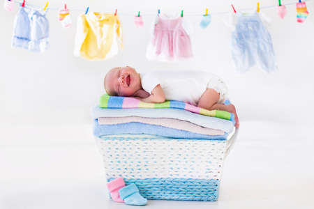 Newborn baby on a pile of clean dry towels. New born child after bath in a towel. Family washing clothes. Kids wear hanging on a line. Infant apparel, textile for children. Smiling boy after shower. Stockfoto