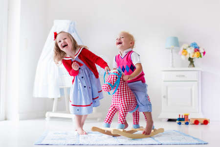 Two children play indoors. Kids riding toy rocking horse. Boy and girl playing at day care or kindergarten. Beautiful nursery for baby and toddler. Toys for preschool child. Brother and sister at home