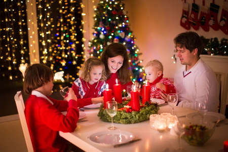 christmas fireplace: Big family with three children celebrating Christmas at home. Festive dinner at fireplace and Xmas tree. Parent and kids eating at fire place in decorated room. Child lighting advent wreath candle.
