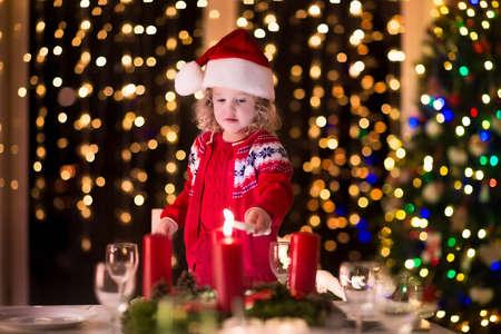 camino natale: Cena di Natale a casa. Bambino accendere una candela sulla corona di Avvento a vigilia di Natale. Decorato soggiorno con camino e albero. Sera d'inverno a camino per famiglie con bambini. I bambini che celebra.