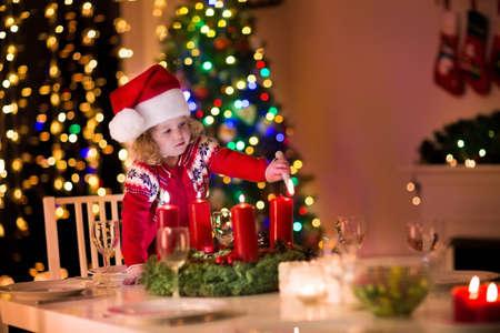 corona navidad: La cena de Navidad en casa. Niño encendiendo una vela en la corona de adviento en la víspera de Navidad. Sala de estar decorada con chimenea y el árbol. Noche de invierno en la chimenea para una familia con niños. Niños celebrando.