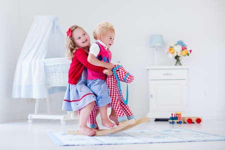preescolar: Dos niños juegan en el interior. Niños montar juguete caballito de madera. Niño y niña jugando en la guardería o jardín de infancia. Hermosa guardería para el bebé y niño pequeño. Juguetes para niños de preescolar. Hermano y hermana en casa
