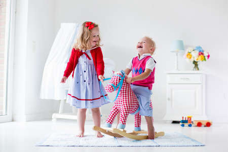 sister: Two children play indoors. Kids riding toy rocking horse. Boy and girl playing at day care or kindergarten. Beautiful nursery for baby and toddler. Toys for preschool child. Brother and sister at home