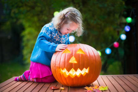 trick or treating: Little girl carving pumpkin at Halloween. Dressed up child trick or treating. Kids trick or treat. Child in witch costume playing in autumn park. Toddler kid with jack-o-lantern.