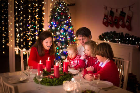 family with three children: Big family with three children celebrating Christmas at home. Festive dinner at fireplace and Xmas tree. Parent and kids eating at fire place in decorated room. Child lighting advent wreath candle.