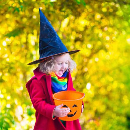 bruja: Ni�a en traje de la bruja jugando en el parque oto�o. Ni�o que se divierte en la baza de Halloween o tratar. Los ni�os truco o trato. Chico Ni�o con jack-o-lantern. Los ni�os con cubo de caramelo en el bosque de oto�o. Foto de archivo