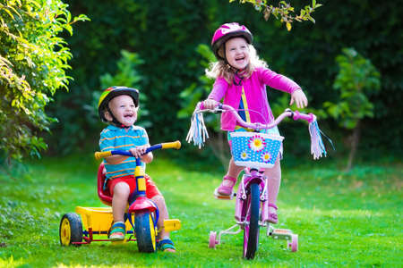 Kids riding bikes in a park. Children enjoy bike ride in the garden. Girl on a bicycle and little boy on a tricycle in safety helmet playing together outdoors. Preschool child and toddler kid biking. Stockfoto