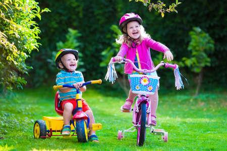 Kinderen paardrijden fietsen in een park. Kinderen genieten van fietsen in de tuin. Meisje op een fiets en kleine jongen op een driewieler in veiligheidshelm buiten spelen samen. Peuter kind en peuter jongen fietsen. Stockfoto