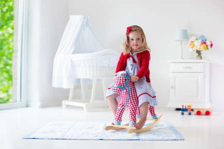 girl on horse: Children play indoors. Kids riding toy rocking horse. Little girl playing at day care or kindergarten. Beautiful nursery for baby and toddler. Toys for preschool child. Cute kid having fun at home