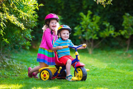 Kids riding bikes in a park. Children enjoy bike ride in the garden. Girl on a bicycle and little boy on a tricycle in safety helmet playing together outdoors. Preschool child and toddler kid biking. Stock Photo