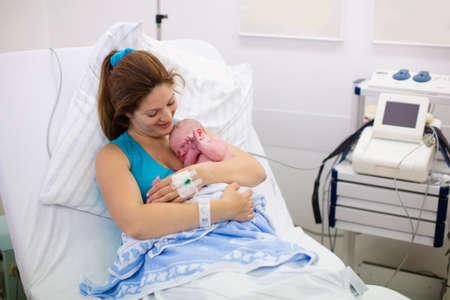 nato: Madre che dà alla luce un bambino. Neonato in sala parto. La mamma tiene il suo bambino appena nato dopo il parto. Femmina paziente incinta in un moderno ospedale. Genitori e infantile primi momenti di legame.