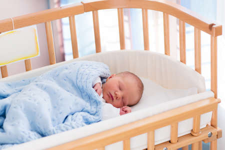 bebes: Bebé recién nacido en la habitación del hospital. Nueva niño nacido en cuna de madera co-sleeper. Dormir infantil en la cuna junto a la cama. Segura co-durmiendo en una cuna junto a la cama. Niño pequeño que toma una siesta bajo la manta de punto.