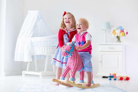 kinder: Dos niños juegan en el interior. Niños montar juguete caballito de madera. Niño y niña jugando en la guardería o jardín de infancia. Hermosa guardería para el bebé y niño pequeño. Juguetes para niños de preescolar. Hermano y hermana en casa