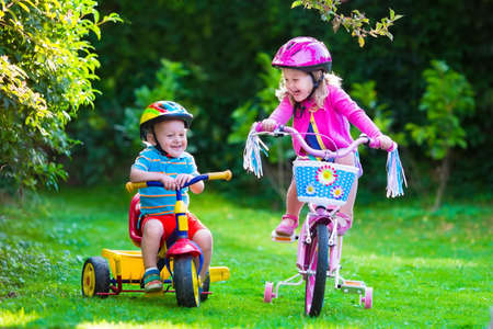 outdoor: Kids riding bikes in a park. Children enjoy bike ride in the garden. Girl on a bicycle and little boy on a tricycle in safety helmet playing together outdoors. Preschool child and toddler kid biking. Stock Photo