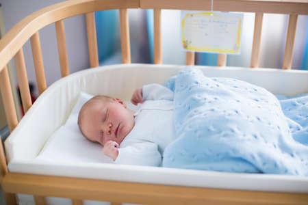 Bambino appena nato in stanza d'ospedale. Nuovo bambino nato in legno co-sleeper presepe. Infante addormentato nel letto culla. Sicuro co-dormire in un lettino con sponda scomparsa. Ragazzino schiacciando un pisolino sotto coperta a maglia. Archivio Fotografico - 43359779