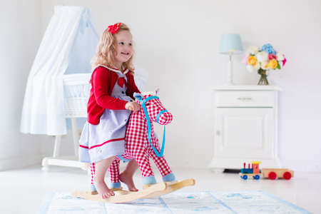 Children play indoors. Kids riding toy rocking horse. Little girl playing at day care or kindergarten. Beautiful nursery for baby and toddler. Toys for preschool child. Cute kid having fun at home