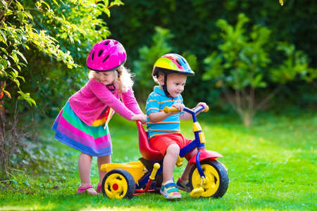day care: Kids riding bikes in a park. Children enjoy bike ride in the garden. Girl on a bicycle and little boy on a tricycle in safety helmet playing together outdoors. Preschool child and toddler kid biking. Stock Photo