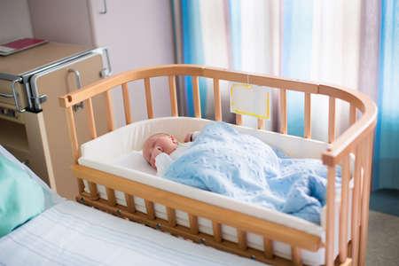 Pasgeboren baby in het ziekenhuis kamer. Nieuw geboren kind in houten co-sleeper wieg. Zuigeling slapen in bed wieg. Veilige co-slapen in een bed kant inbegrepen. Kleine jongen een dutje doen onder gebreide deken. Stockfoto