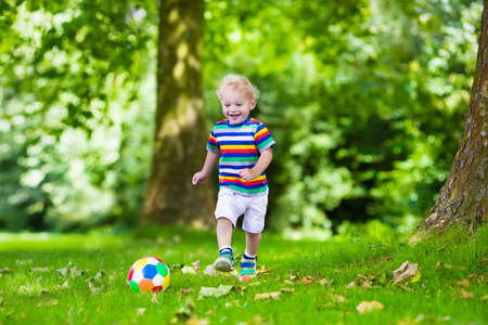 Gelukkig kind spelen Europees voetbal in openlucht in schoolplein. Kinderen voetballen. Actieve sport voor voorschoolse kind. Bal spel voor jong kind team. Jongen een doelpunt in het voetbal wedstrijd.