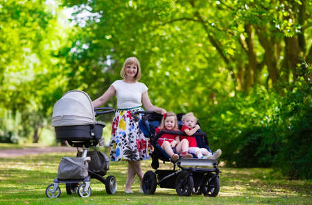 Young mother walking in a park with children in pushchair. Mom and kids in a buggy walk in forest. Woman pushing a double stroller for twin boy and girl and newborn baby. Active family outdoors.