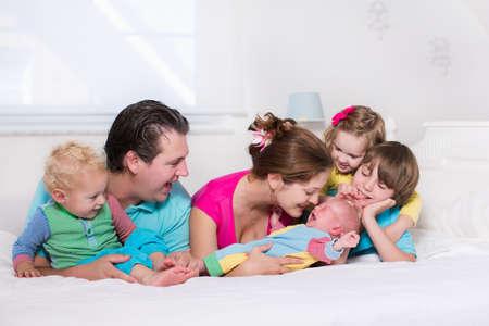 Grote familie met vier kinderen ontspannen in bed op een zonnige ochtend. Ouders met pasgeboren baby, peuter jongen, kleuter meisje en tiener zoon in een witte slaapkamer. Moeder en vader spelen met kinderen. Stockfoto - 43360230