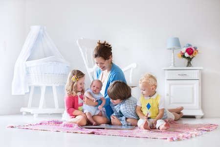 bassinet: Mother and children play indoors. Family with kids in a white bedroom. Mom with baby, boy and girl playing and reading books at home. Beautiful nursery for baby and toddler. Room for preschool child. Stock Photo