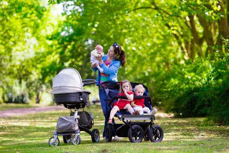 niño empujando: Madre joven caminando en un parque con los niños en cochecito. Mamá y los niños en un paseo con errores en el bosque. Mujer que empuja un cochecito doble para el muchacho gemelo y una niña y el bebé recién nacido. Familia activa al aire libre.